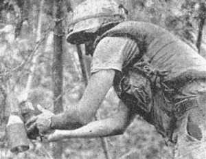 "An American soldier attempting to destroy a Viet Cong explosive ""booby trap""."